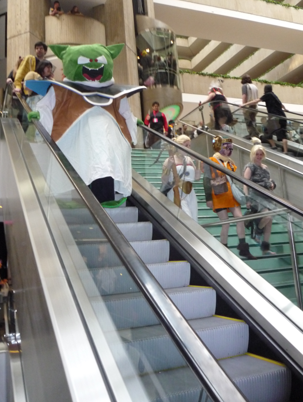 A group of Chrono Trigger cosplayers at ACen 2010.  Marle and Ayla are walking down the stairs while Ozzie takes the escalator.