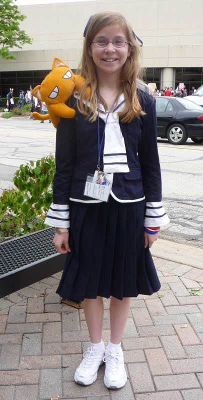 A young Honda Tohru cosplayer at ACen 2010 with a Kyo cat doll