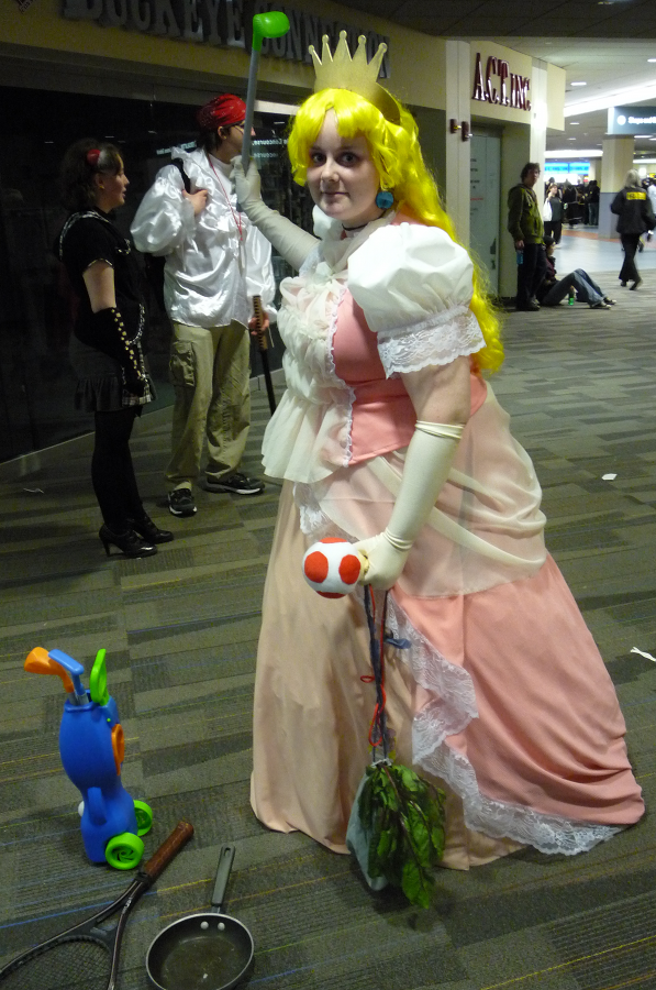 A Princess Peach cosplayer brandishing a golf club at Ohayocon 2010